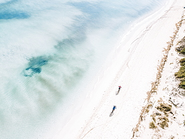 Aerial view of two cyclists riding mountain bikes on a white sand beach, Mallorca, Balearic Islands, Spain