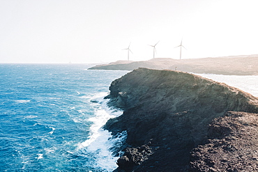 Rugged stretch of coastline with wind turbines on background, Tenerife, Canary Islands, Spain