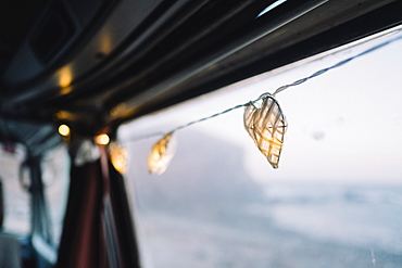 Lit string lights hang from camper van door, Tenerife, Canary Islands, Spain