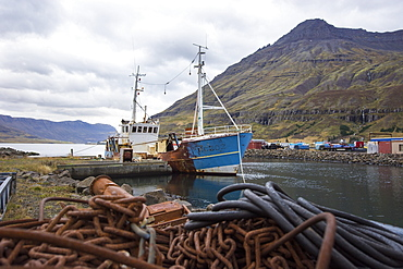 Rusty chains in front of old abandoned fishing boat moored in harbor of small coastal town, Seydisfjordur, Iceland