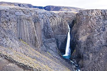 Scenic view of Litlanesfoss waterfall and surrounding cliffs of Hengifoss walking track, Iceland