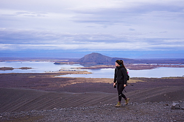 A young woman dressed in black and wearing boots walks along the ridge of the Hverfjall crater with Lake Myvatn in the background.