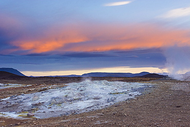 A blue coloured boiling hot mud pool emanates steam as the sunset colours the sky orange, in Hveraröndor Hverir Geothermal Area at Namaskard Pass, North Iceland.