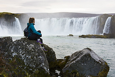 Portrait of female hiker sitting on rocks and looking at splashing Godafoss waterfall, Iceland
