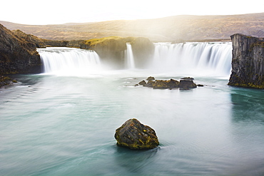 Long exposure of scenic Godafoss waterfall lit by golden sunlight at dusk, Iceland