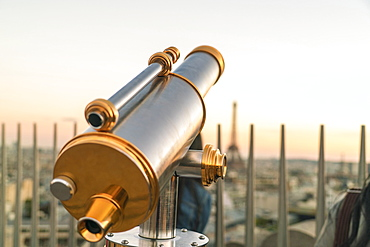 Viewing telescope against clear sky at sunset on Triumphal Arch, Paris, France