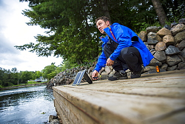 Man crouching on harbor and setting up solar panel to recharge battery, Washego, Ontario, Canada