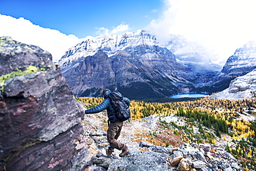 Male backpacker hiking in Yoho National Park with scenic landscape in background, Field, British Columbia, Canada