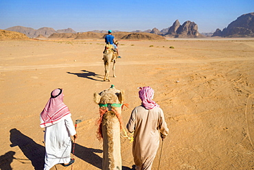First person perspective riding camel through desert of Wadi Rum, protected desert wilderness in southern Jordan, with sandstone mountains and man riding camel in distance, Wadi Rum Village,  Aqaba Governorate, Jordan