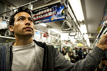 Man standing in subway car full of people, Tokyo, Japan
