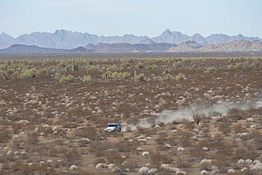 Jeep driving along path in barren desert landscape, Sonora, Mexico