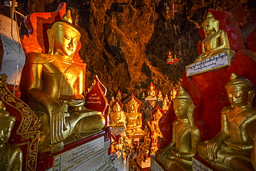 Gold Buddha statues line the sides of the famous Pindaya Caves in Shan State, Myanmar. The cave is a common tourist destination and pilgrimage site for Buddhists.