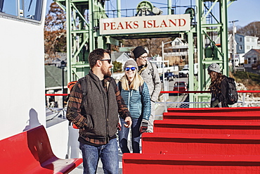 Group of happy friends getting off ferry, Peaks Island, Maine, USA