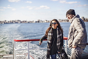 Two friends leaning on railing while riding ferry to Peaks Island, Portland, Maine, USA