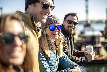 Portrait of young woman wearing sunglasses laughing while waiting with friends at harbor, Portland, Maine, USA