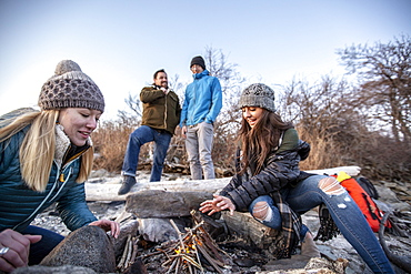 Four adult friends relaxing around campfire while camping on coastal beach in autumn, Portland, Maine, USA