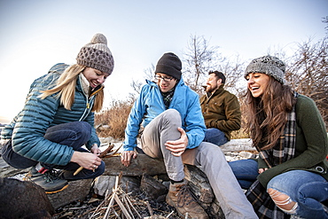 Four adult friends preparing campfire on coastal beach in autumn, Portland, Maine, USA