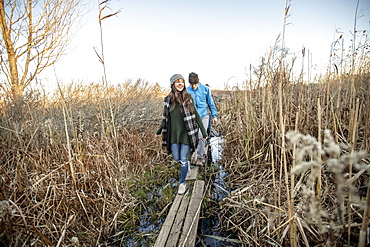 Young couple crossing narrow boardwalk during hikethrough tall grass, Portland, Maine, USA
