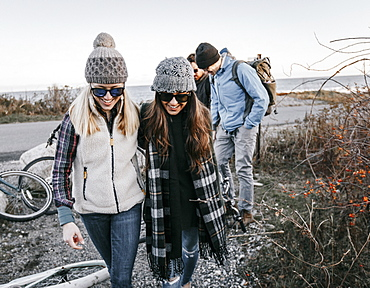 Group of adult friends leaving bicycles and walking beside bushes during hike, Portland, Maine, USA
