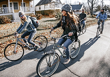 Group of friends biking through sunny village in autumn, Portland, Maine, USA