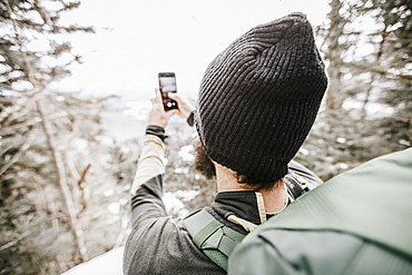 Hiker wearing wooly hat taking cell phone picture in mountain in winter, Whiteface, New Hampshire, USA