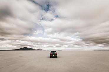Lone car driving along expansive desolate Salt Flats, Wendover, Utah, USA