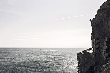 Man climbing on Otter Cliffs overlooking sea, Acadia National Park, Maine, USA