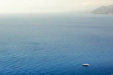 Lone boat anchored inpristine Mediterranean Sea off Italy coastline, , Camogli, Liguria, Italy