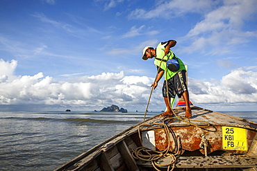 A boat captain raises the anchor on a boat along that coast of Krabi, Thailand before a ride to Railay Beach, a popular tourist destination.