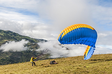 Distant view of adventurous man getting ready to?paraglide?down a mountain in?Paute Canton, Azuay Province, Ecuador