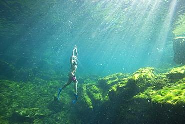 Underwater view?of woman in bikini snorkeling,?Cenote?el Eden, Riviera Maya,?Playa?del?Carmen,?Quintana?Roo,?Mexico