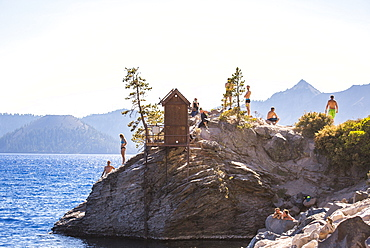 Swimmers wait on a rock outcrop surrounded by a big blue lake on sunny summer day, Crater Lake, Oregon, USA