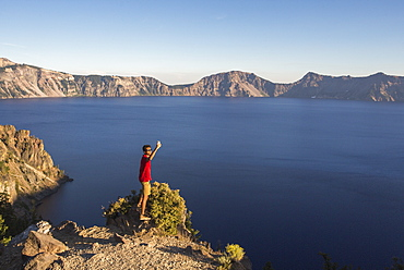 A young man in a red shirt poses for a selfie on a rock outcrop high above a deep blue lake surrounded by mountains, Crater Lake, Oregon, USA