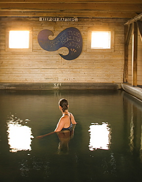 A woman soaks in an indoor hot spring in an old barn building, Summer Lake, Oregon, USA
