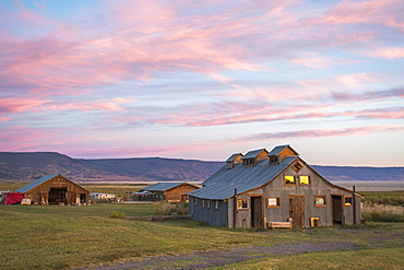 An old barn set in a grassy field under a pink and blue sunset sky, Summer Lake, Oregon, USA