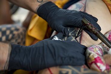 Close-up?shot of hands of Hawaiian tattoo artist making tattoo, Oahu, Hawaii Islands, USA