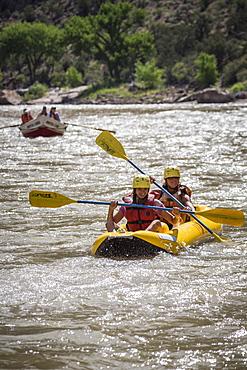 A young girl and her mother paddling an inflatable kayak, Green river rafting trip, Desolation/Gray Canyon section, Utah, USA