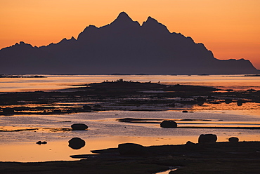 Scenic landscape with silhouette of Vogakallen mountain peak at sunset, Lofoten Islands, Norway