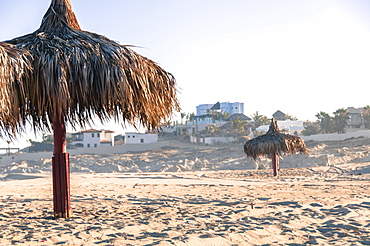 View of two thatched umbrellas on beach, Cabo San Lucas, Baja California Sur, Mexico