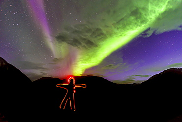 View of light painted human shape under aurora borealis, Narsaq, Greenland