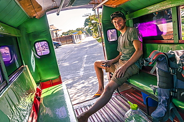 Smiling young man sitting in motor rickshaw and looking at camera,  Chiang Mai, Thailand