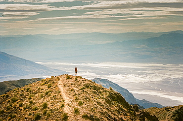 A man stands on a peak looking out over Death Valley at Dantes View, California, USA