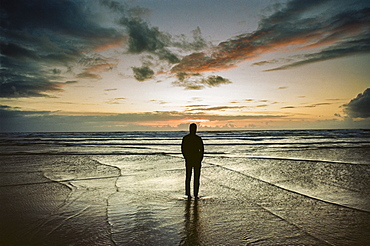 A man stands on the beach watching the waves and sunset over the Pacific Ocean, Oregon, USA