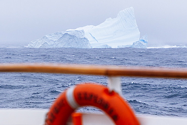 An iceberg seen from a passing ship in a storm 12 miles off the coast of the Westfjords in Iceland