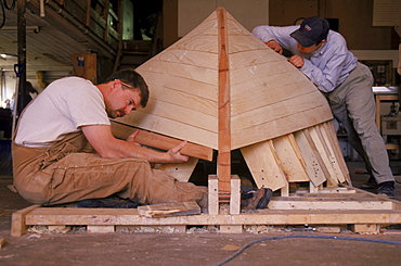 Students at the Landing School construct the hull of a small peapod design boat in Arundel, Maine.