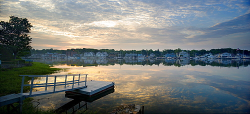Morning clouds reflect in Rowayton Harbor as the sun just crests the horizon. Rowayton, a waterfront community of Norwalk, CT, is home to many sailors and fishermen and is about 45 miles up Long Island Sound from New York City.