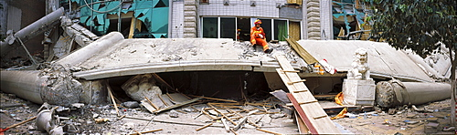 A rescue worker takes a break on top of a collapsed roof May 16 in Beichuan, China. The death toll in China's worst earthquake in 30 years could top 80, 000 according to the government.