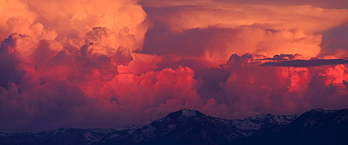 Pink, orange and red thunderheads over Lake Tahoe and the Sierra mountains in the evening