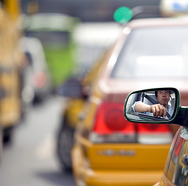 A taxi driver waits in a traffic jam in Beijing,
