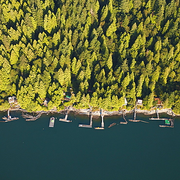 Looking down on a row of waterfront cabins that line the shores of Pitt Lake in British Columbia, Canada.